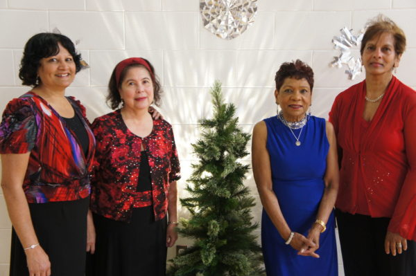 A group of female seniors smiles for a group photo by a Christmas Tree