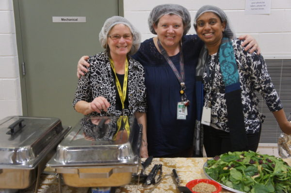 MFRC Staff joins together for a photo at the buffet line while serving food.