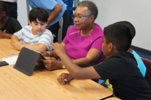 Children teaching seniors about tablet s